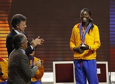 Caterine Ibarguen, silver medallist in the women's triple jump event at the London 2012 Olympic Games, is applauded by President Juan Manuel Santos (L top) after being decorated with the Order of Boyaca medal during a ceremony at presidential palace in Bogota August 15, 2012. Colombia won eight medals in total in the London Olympics.