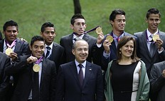 Mexican President Felipe Calderon (first row, C) and his wife Margarita Zavala (R) pose with Mexico's Olympic gold medalist soccer players and coaches, after attending a dinner at Los Pinos Presidential Palace in Mexico City August 15, 2012. Mexico beat Brazil in their men's soccer final gold medal match at the London 2012 Olympic Games.