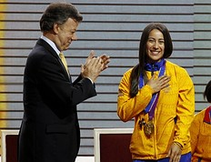 Mariana Pajon, gold medallist in the women's BMX event at the London 2012 Olympic Games, is applauded by Colombian President Juan Manuel Santos after being decorated with the Order of Boyaca medal during a ceremony at presidential palace in Bogota August 15, 2012. Colombia won eight medals in total in the London Olympics.