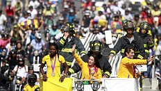 Mariana Pajon (C), gold medallist in the women's BMX event, Carlos Oquendo (L), bronze medallist in the men's BMX event, and Caterine Ibarguen (R), silver medallist in the women's triple jump at the London 2012 Olympic Games, attend a parade on a fire truck in Medellin, August 16, 2012. Colombia won eight medals in total at the Olympic Games in London.