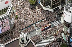 An aerial view shows London Olympic medalists atop an open-top bus parading through Japan's Ginza shopping district as people pack the streets in Tokyo in this photo taken by Kyodo August 20, 2012. Japan held its first Olympic parade on the streets of Tokyo for its' returning medalists as the city eyes hosting the games of 2020. Mandatory Credit.
