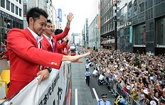The 4x100m medley relay silver medallist Kosuke Kitajima (L) waves to crowds of people from an open-top bus during a parade by Japan's 2012 London Olympic Games medallists at Tokyo's upmarket Ginza street on August 20, 2012. The Japan Olympic Committee (JOC) held the first ever Olympic medallists parade hoping it will boost the city's bid to host the 2020 Summer Games.