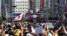Japan's medallists (C) at the London 2012 Olympic Games wave to a crowd of people from open-top buses during a parade at Tokyo's upmarket Ginza street on August 20, 2012. The Japan Olympic Committee (JOC) held the first ever Olympic medallists parade hoping it will boost the city's bid to host the 2020 Summer Games.