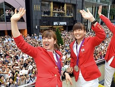 Japan's women's badminton doubles silver medallists Mizuki Fujii (L) and Reika Kakiiwa (R) wave to crowds of people from an open-top bus during a parade by Japan's 2012 London Olympic Games medallists at Tokyo's upmarket Ginza street on August 20, 2012. The Japan Olympic Committee (JOC) held the first ever Olympic medallists parade hoping it will boost the city's bid to host the 2020 Summer Games.