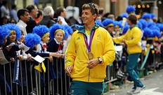 An unidentified Australian Olympian (C) walks past spectators as the Australian Olympic team was officially welcomed home from the 2012 London Olympic Games with a colourful street parade through Sydney on August 20, 2012. Australia finished 10th on the medal table, a slump from its performance in Beijing where it claimed 6th position, leading to a rush of criticism that the team underperformed.