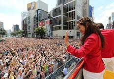 Japan's women's football silver medallist Homare Sawa (R) waves to crowds of people from an open-top bus during a parade by Japan's 2012 London Olympic Games medallists at Tokyo's upmarket Ginza street on August 20, 2012. The Japan Olympic Committee (JOC) held the first ever Olympic medallists parade hoping it will boost the city's bid to host the 2020 Summer Games.