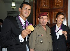 Tunisian Chief of staff, General Rachid Ammar (C), poses with Olympic silver medalist Habiba Ghribi (R) and Olympic champion, swimmer Oussama Mellouli (L), in Tunis on August 21, 2012. Habiba Ghribi won silver medal in the 3000m steeplechase while Oussama Mellouli won the men's 10km swimming marathon during the London 2012 Olympic Games.