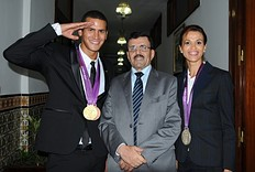 Tunisian Interior Minister Ali Larayedh (C) poses with Olympic silver medalist Habiba Ghribi (R) and Olympic champion, swimmer Oussama Mellouli (L), in Tunis on August 21, 2012. Habiba Ghribi won silver medal in the 3000m steeplechase while Oussama Mellouli won the men's 10km swimming marathon during the London 2012 Olympic Games.