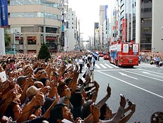 Crowds of people wave to Japan's Olympic medallists riding on open-top buses (R) during a parade at Tokyo's upmarket Ginza street on August 20, 2012. The Japan Olympic Committee (JOC) held the first ever Olympic medallists parade hoping it will boost the city's bid to host the 2020 Summer Games.